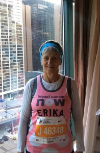 Woman in hotel room wearing running kit and race number
