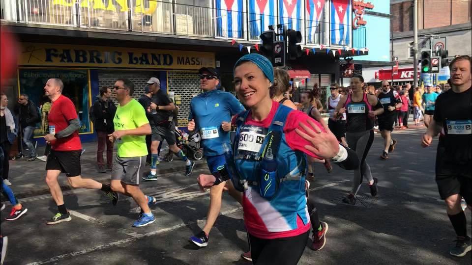 female runner in race waving to camera